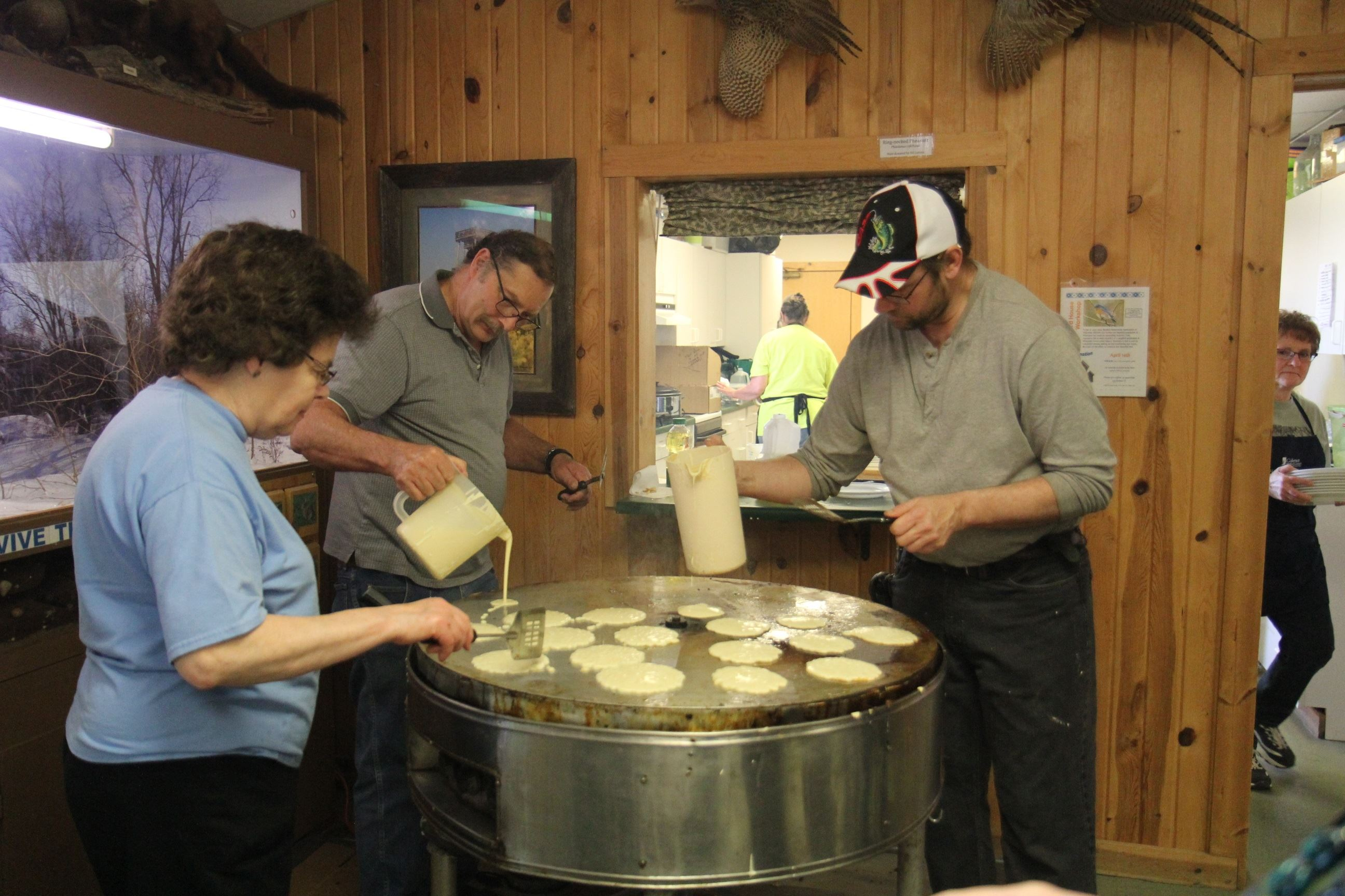 3 people pouring pancake batter onto a large round cooker