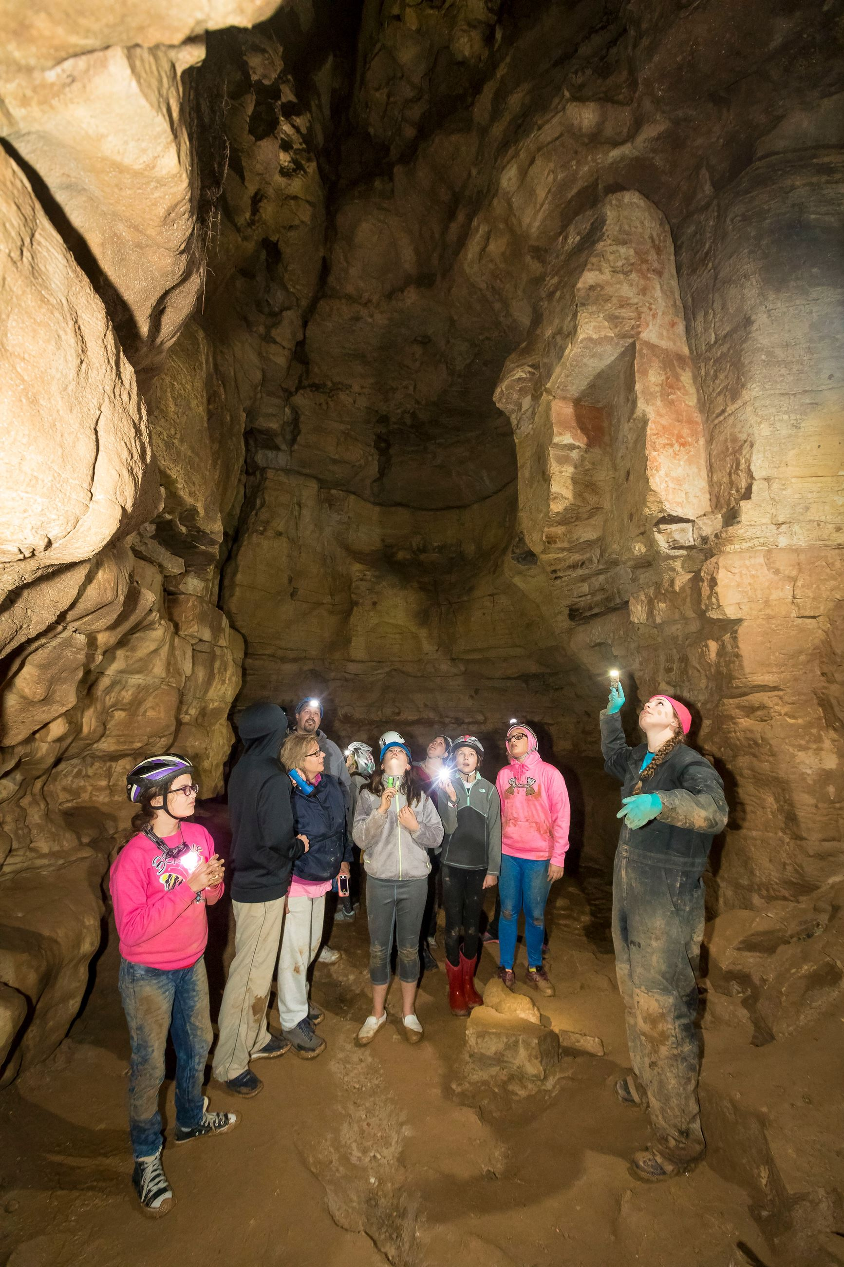 An instructor and a group of teenage girls standing in a large cave. They are all looking up.