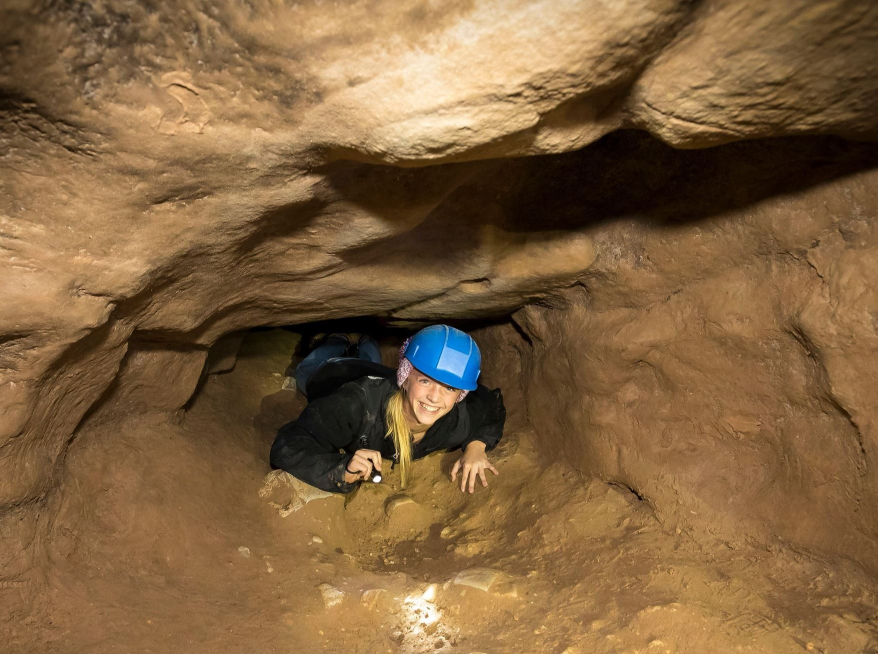 A girl wearing a blue helmet and holding a flashlight is crawling on her belly through a tunnel in a