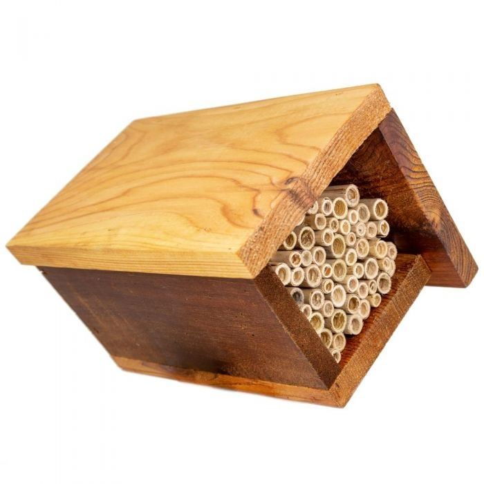 A cube shaped native-bee-house made from wood and reeds
